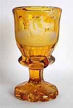 A BOHEMIAN SMOKEY AMBER GLASS GOBLET engraved with a recumbent stag and on