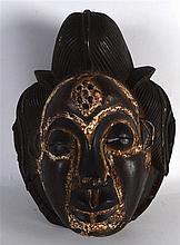 A CARVED AND POLYCHROMED AFRICAN MASK with rope twist mounts. 11.5ins long.
