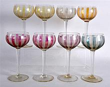 A SUITE OF EIGHT VENETIAN GLASSES with yellow, puce and blue glass panels.