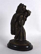 A NOVELTY BRONZE INKWELL in the form of a roaming hooded male. 8.5ins high.