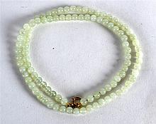 A 24.5INCH GREEN BEADED NECKLACE with 9ct gold clasp.