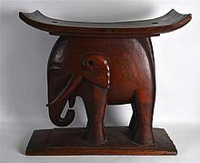 A LARGE CARVED HARDWOOD ETHNIC STOOL in the form of a standing elephant upo