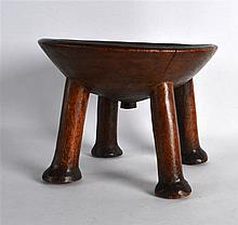 AN EARLY 20TH CENTURY CARVED HARDWOOD ETHNIC STOOL of circular form upon fo