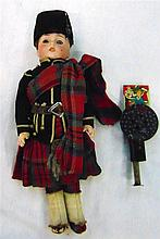 A SCOTTISH BISQUE HEAD DOLL, together with a tin plate toy. (2)