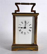 A SMALL BRASS CARRIAGE CLOCK with white dial and black numerals. 5.75ins hi