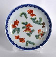A CHINESE DOUCAI PORCELAIN SAUCERDISH painted with fish amongst reeds. Sign