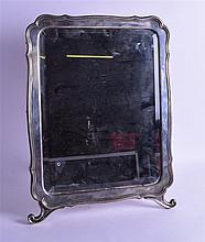 A VERY LARGE LATE 19TH CENTURY RUSSIAN SHAPED SILVER MIRROR supported upon splayed feet. 36 cm x 49 cm.