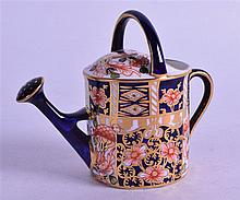 A ROYAL CROWN DERBY MINIATURE WATERING CAN, painted in imari pattern. 9 cm wide.