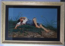 A LARGE FRAMED CANADIAN NEEDLWORK STUDY OF A YOUNG BOY modelled reclining within a landscape. Image 2ft 7ins x 1ft 6.5ins.   Note: Stitched by an inmate at Kingston Penitentiary, Ontario, Canada