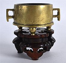AN EXTREMELY RARE CHINESE QING DYNASTY MINIATURE BRONZE CENSER bearing Xuande marks to base, supported upon a fitted hardwood base. 82 grams. Overall 2.5ins wide, internal diameter 1.5ins.