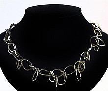 Long collier en argent fait de maillons imbriqués en forme de feuille. Poin