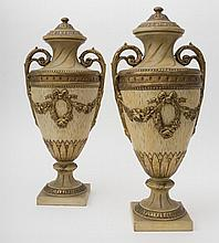 Pair of large, covered Neoclassical vases Baluster shape, in distressed terracotta, with rich décor of flowering branches and stylized floral friezes. Each has bilateral handles and rests on a round, flared base and a square stand. H: 56 cm, D: 26