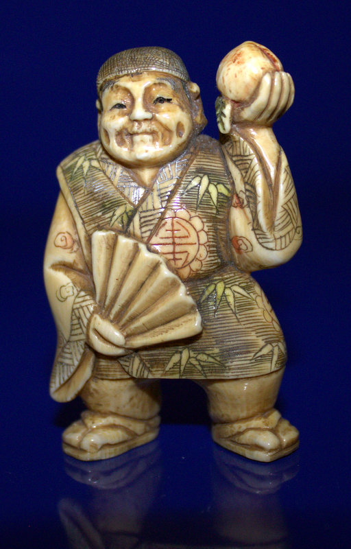 A Meiji Period Stained Ivory Netsuke Of A Man Holding A Peach, Signed To Base With Red Signature