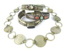 Three antique Sino-Tibetan white metal bangles and an Indo-Chinese coin bra