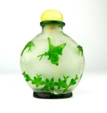 A Peking cameo green over grey glass snuff bottle decorated with butterflies, 8cm high.