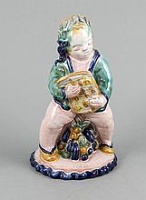 Art-Déco-Keramikfigur eines singenden Puttos, Werkstatt Rudolf Sommerhuber, Österreich, Steyr, um 1920-1930, Fayence bzw. Irdenware mit weißer Zinnglasur sowie polychromer Bemalung, auf einer runden Plinthe mit Früchtebukett stehender,