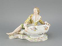 Figürliche Konfektschale, Meissen, Marke 1850-1924, 2. W., nach einem Entwurf von Johann Joachim Kaendler (1706 Dresden - 1775 Meißen), um 1762, Modellnr. 2863, an einer ovalen Konfektschale lagernder, im Stil des Rokoko gekleideter Kavalier,