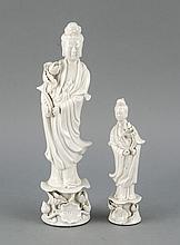 Zwei Guanyin-Figuren, China, 20. Jh., Blanc de chine, auf einer Lotusblume stehende Figuren, Finger best., H. 16 und 26 cm