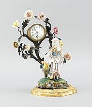 Dekorative Kaminuhr, rundes Uhrwerk in einem Metallast, besetzt mit Porzellanblumen min. best., im Boden eingesetzte Porzellanfigur, 'Hühner fütterndes Mädchen', Passau um 1900, auf naturalistischem Sockel, nach einem Entwurf von Melchior, Hoechst