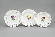 Drei Durchbruchteller, Meissen, Marke 1970-80, 2. W., polychrome Blumenmalerei im Spiegel und in drei Kartuschen, Goldrand, D. 18 u. 21 cm