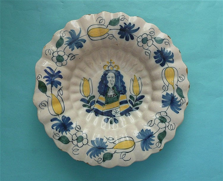 William III: a Dutch Delft polychrome fluted dish painted with a central po