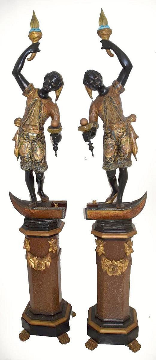 Pair of 19th Century Italian Carved Gilt Wood Blackamoors - Each is standing on a half of a gondola (that come together to form a singular boat). painted & gilded w/ Venetian glass accents - Each is holding a lit torch in one uplifted hand and a