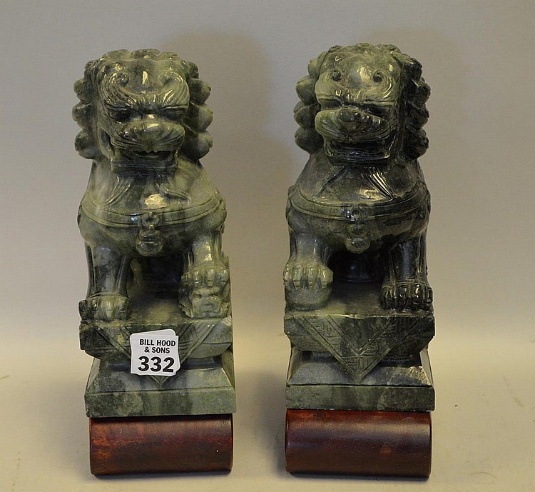 Pair of green stone foo dogs. 8 in. tall x 5in. long x 3-1/2 wide, 1-1/2 tall wood stands