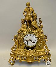 Antique Gilt Bronze Figural Medieval Knight Themed Clock - Time & Strike movement, enameled porcelain clock face. Features a man in regal knight garb, with his weapon, armor, and shield resting on a rock beside him. Ornate foliate and scroll