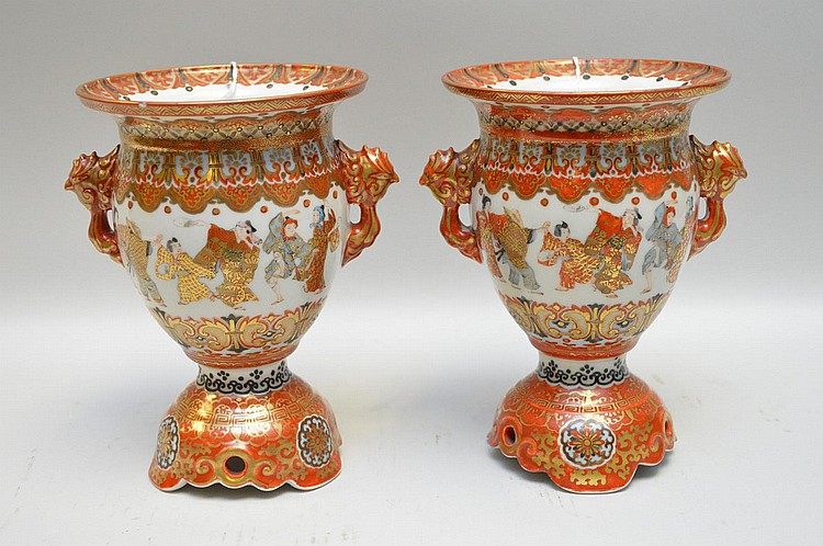 Pair of Japanese Kutani Satsuma Pedestal Vases Featuring Kabuki Dancers - Multiple kabuki dancers on each exterior face of the urns among ornate decoration in reds, black, and gold. Stylized bird handles. Red-painted six character marks on bottom.