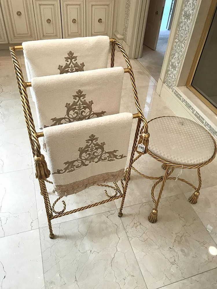 "Gilt Metal Tassel-Form Towel Holder, together with a gilt metal tassel-form stool. Condition: Good, with one stain on upholstery on stool. Dimensions: towel rack - 35 1/2"" H x 18"" W x 15"" D; stool - 19"" H x 15 1/2"" diameter."