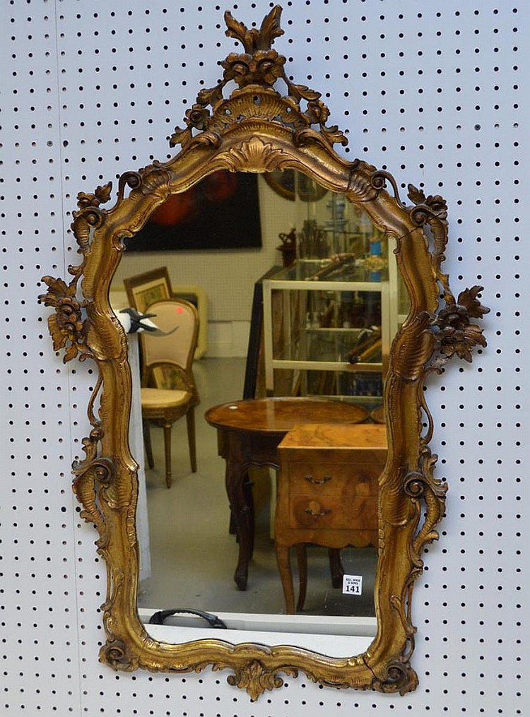 """Carved Italian Gilt Wood Mirror, with floral and scroll motif. Condition: Good, with a slight seam separation, structure is sturdy. Dimensions: 39"""" H x 24"""" W."""