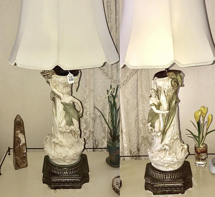 """Pair of Royal Dux Art Nouveau-Form Nymph Porcelain Vases, each features a female beauty reaching towards a flower. Now electrified and mounted as lamps. Condition: Good and working, with no noticeable damage. Dimensions: 25"""" H to socket, 36"""" H"""