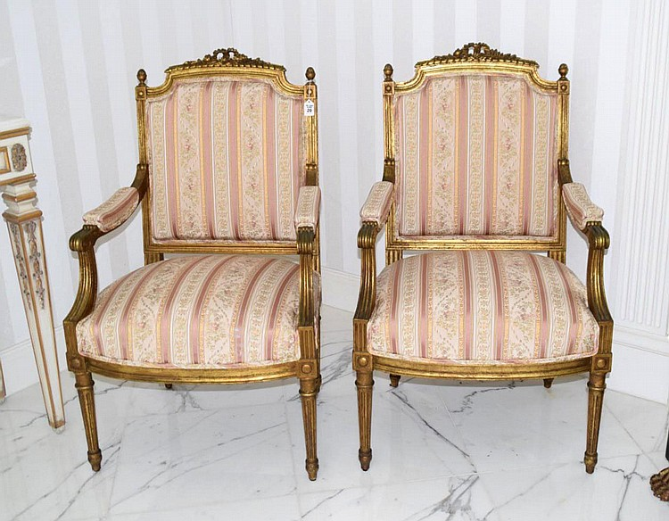 "Pair of French Fauteuil Louis XV-style Gilt Wood Chairs. Features expertly restored period-style fabric upholstery of rose and cream colored bands with tiny floral details. Condition: Very good. Dimensions: 40"" H x 23"" W x 20"" D. Seat height: 19"""