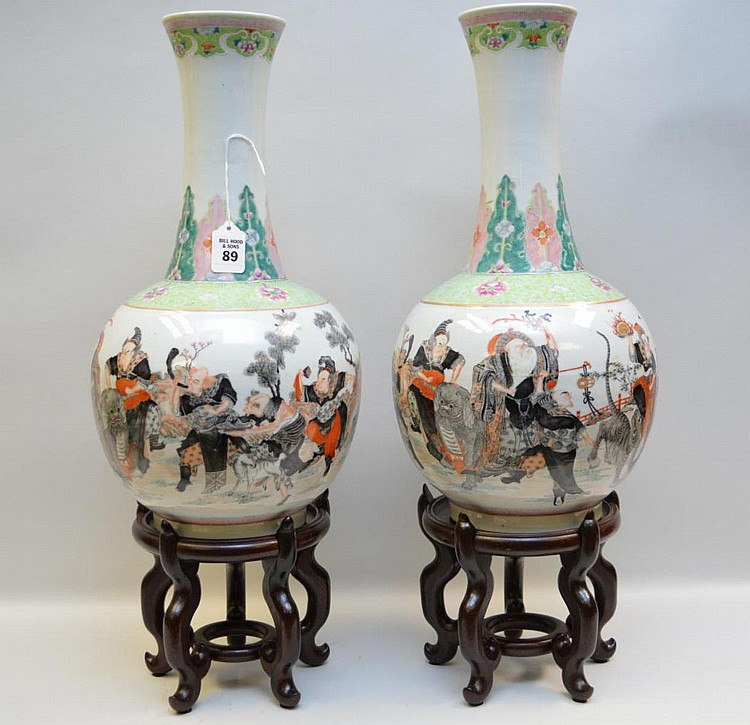 Pair Antique Chinese Porcelain Vases with continuous scene depicting warriors in a landscape scene on a white ground body raising to a floral decorated neck on a white ground. Condition: good with no cracks or chips. Ht. 18