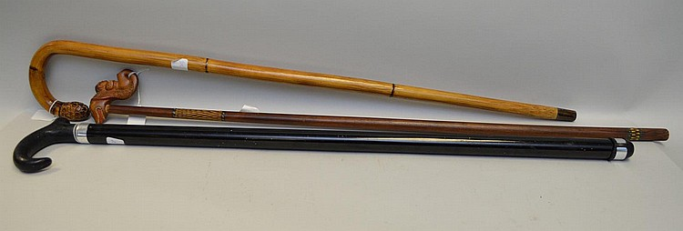 Three Walking Sticks Canes - One lacquered bamboo cane with carved handle 35 3/4