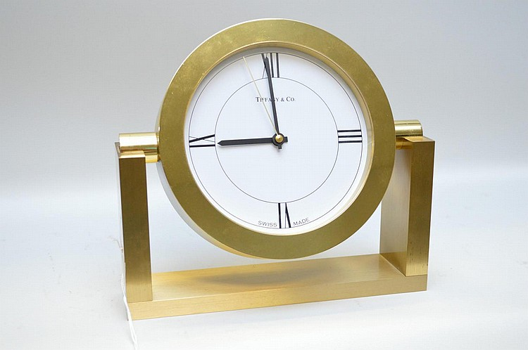 Tiffany & Co. Brass Desk Mantle Clock - Swiss made quartz movement, battery operated. Condition: Good and working. Some scratches on pegs where clock face fits into stand. Dimensions: Clock face 6