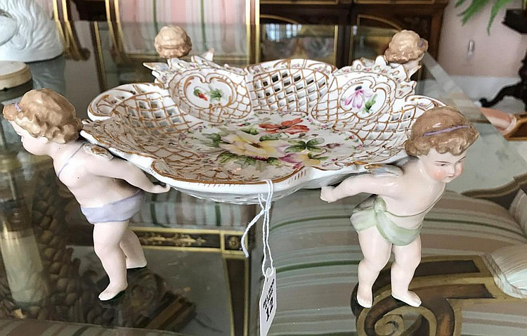 "German Porcelain Figural Center Bowl with Cherub Supports. Pierced Lattice-work on sides of dish surface. Floral motif in center. Condition: Good with no noticeable damage. Dimensions: 5 3/8"" H x 10 1/2"" diameter"