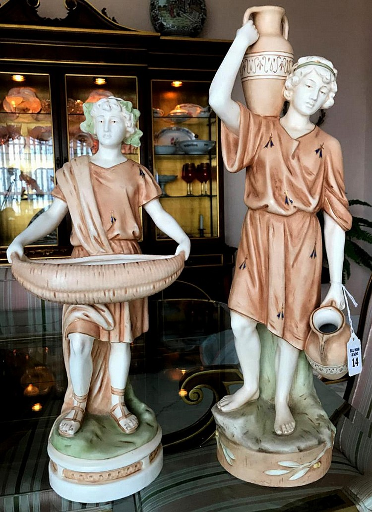 """Pair of Bohemian Porcelain Figures - Boy holding water jug- 20"""" H. Condition: Repair to lower jug handle. Boy with basket- 17"""" H. Condition: Two small hairline crack to the base."""