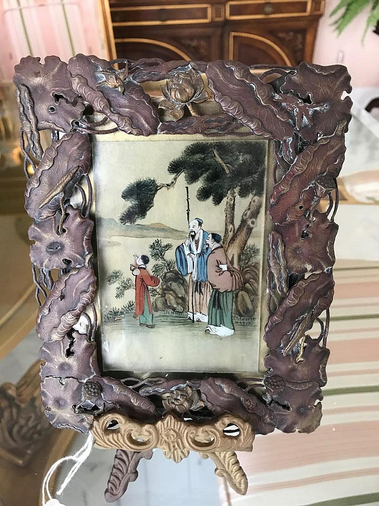 Chinese Painting of two men and one boy on a landscape, reverse painted on glass. Framed in a patinated Art Nouveau Frame. Frame features lotus flowers, lily pads, and birds. Also includes gilt metal stand. Condition: Good with no noticeable damage.