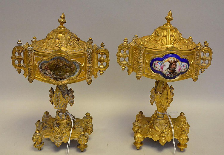 Pair of Antique Gilt Bronze Urns with Royal Portrait - Each of the urns features knight imagery, such as arms and armor. One urn has a porcelain portrait of a king, however the portrait is missing from the other urn. Condition: One missing portrait.