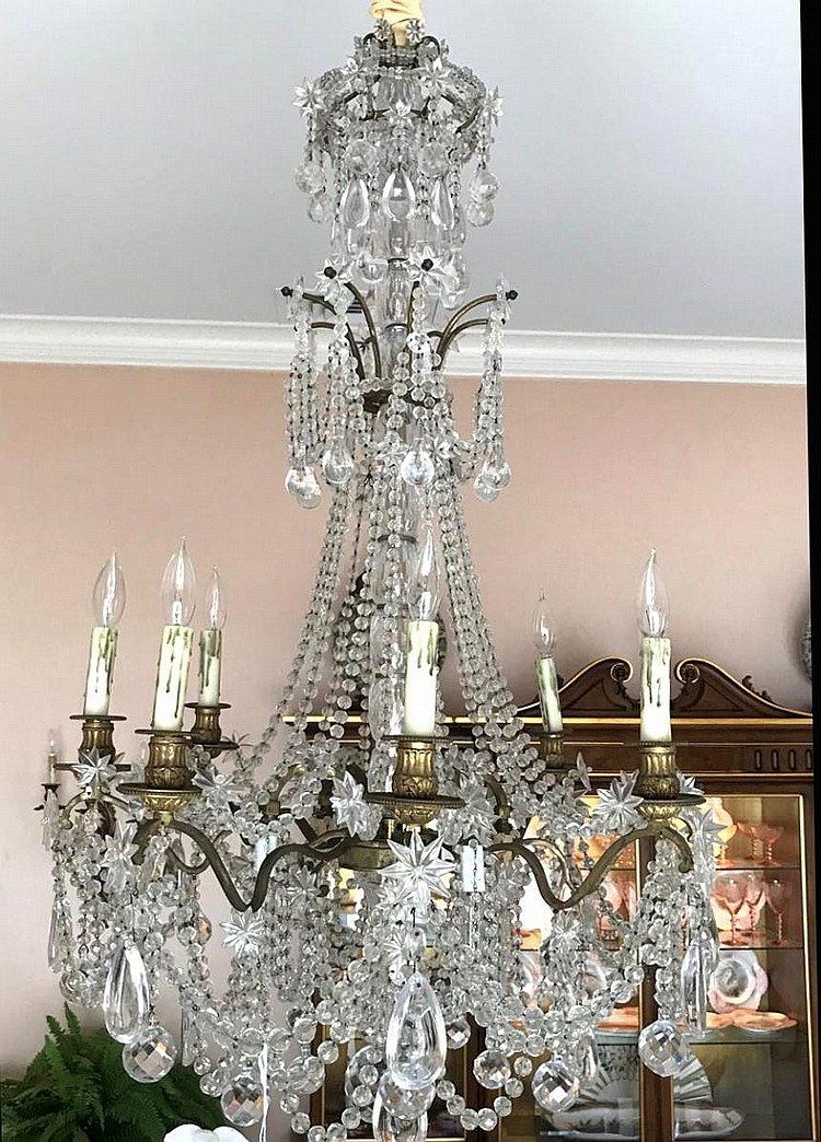 "French Twelve-Light Gilt Bronze & Crystal Chandelier. Hanging prisms of varying sizes and shapes (tear drop, spherical), 8-pointed stars. Condition: Good and working. Dimensions: Approx. 46"" H x 28"" diameter."