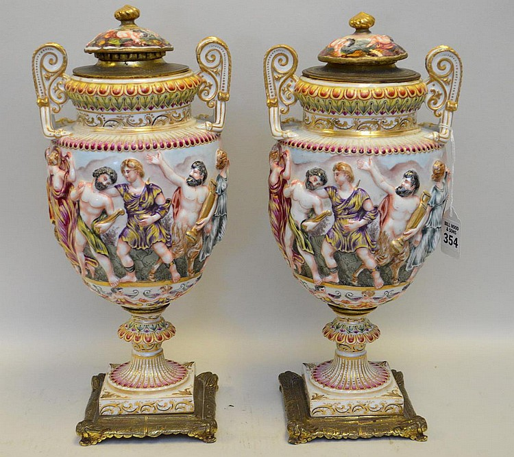 Pair Of Capodimonte Porcelain & Bronze Urns. Condition: one urn has a chip at the stem. Both urns have minor understandable wear. Ht. 14 1/2