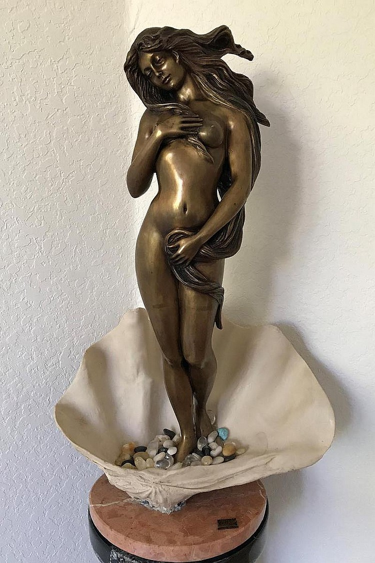 Manuel Vidal, Ebano made in Spain, Bronze nude female standing in shell with polished tumbled loose rocks 34in. Tall x 21 in. wide on rose marble round base