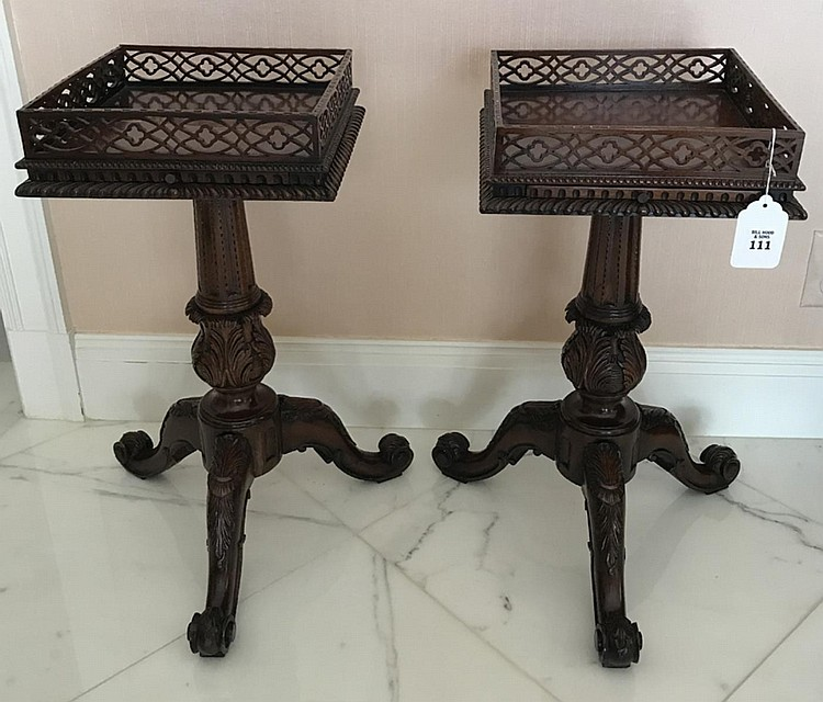 """Pair of Carved Mahogany Chippendale Candle Stands - with tripod base raising to a reticulated gallery top. Condition: One table has an age crack across the top. Dimensions: 23"""" H x 16"""" W x 14"""" D."""