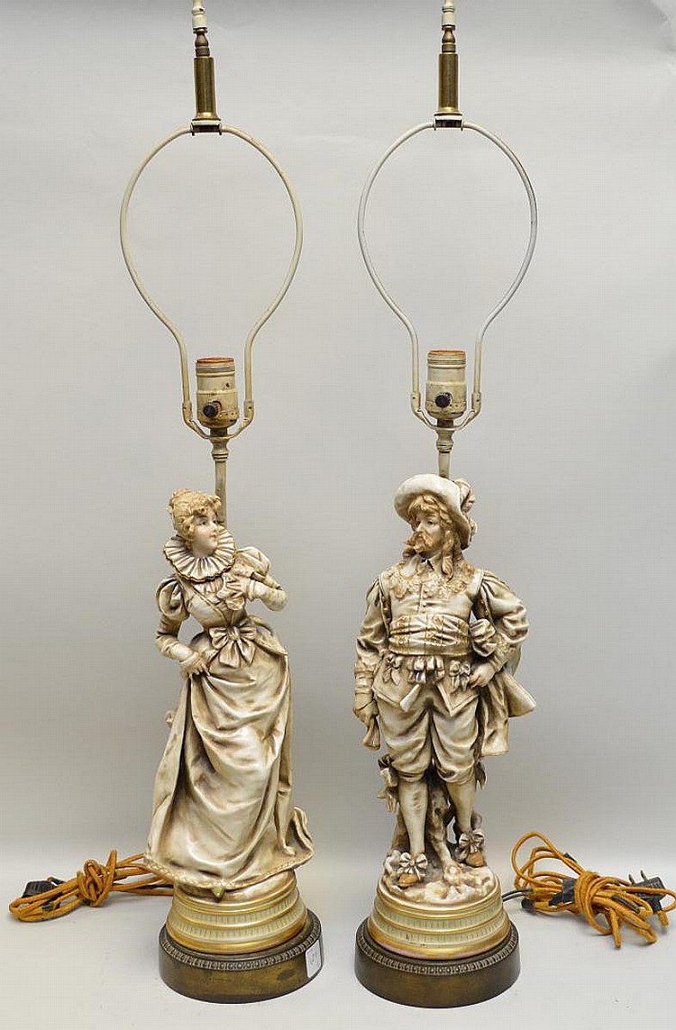 Pair of Ceramic Figural Lamps, depicting a couple in 17th century-style costume. Metal bases. Condition: Male figure has a broken hand, female figure has crack to metal base. Wiring is early and will have to be rewired. Dimensions: male figure 15
