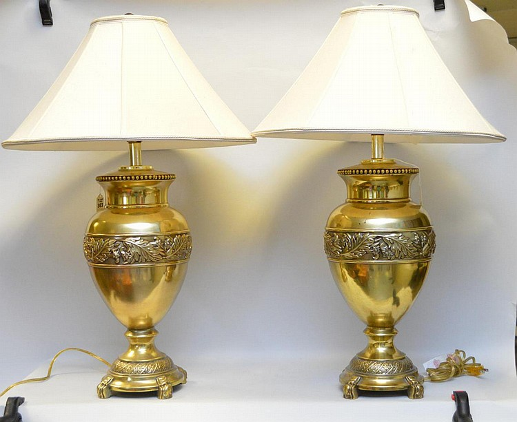 Pair of Brass Urn-Form Lamps, with foliate design in relief. Cream colored raw silk shades. Condition: Good, with minor normal wear, working. Dimensions: 25