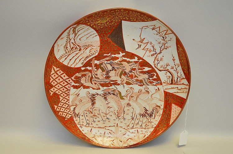 Japanese Kutani Porcelain Charger Depicting Cranes - Ornately decorated in predominantly reds & gilt. Features cranes and landscapes on both surfaces. Red painted six character mark on bottom. Condition: The charger has several well fitted repairs