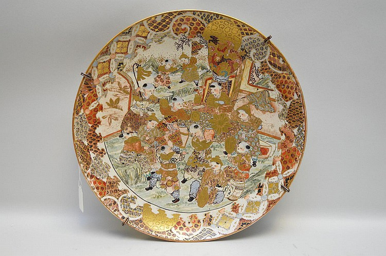 Japanese Satsuma Figural Charger Featuring Children - Ornately decorated on charger surface, underside is plain. Gilt and enamel decoration. Has a metal hanging apparatus. Condition: One small repair to rim. Cracklature to glaze on undecorated white