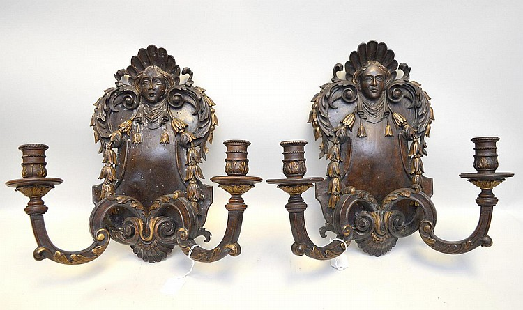 Pair of Regency Carved Wood Two-Light Sconces, features a female face surrounded by shell, scroll, foliate and gilt wood accents on a dark wood base. Condition: Both candelabras have some worm holes, but one has more than the other. Some residual wax