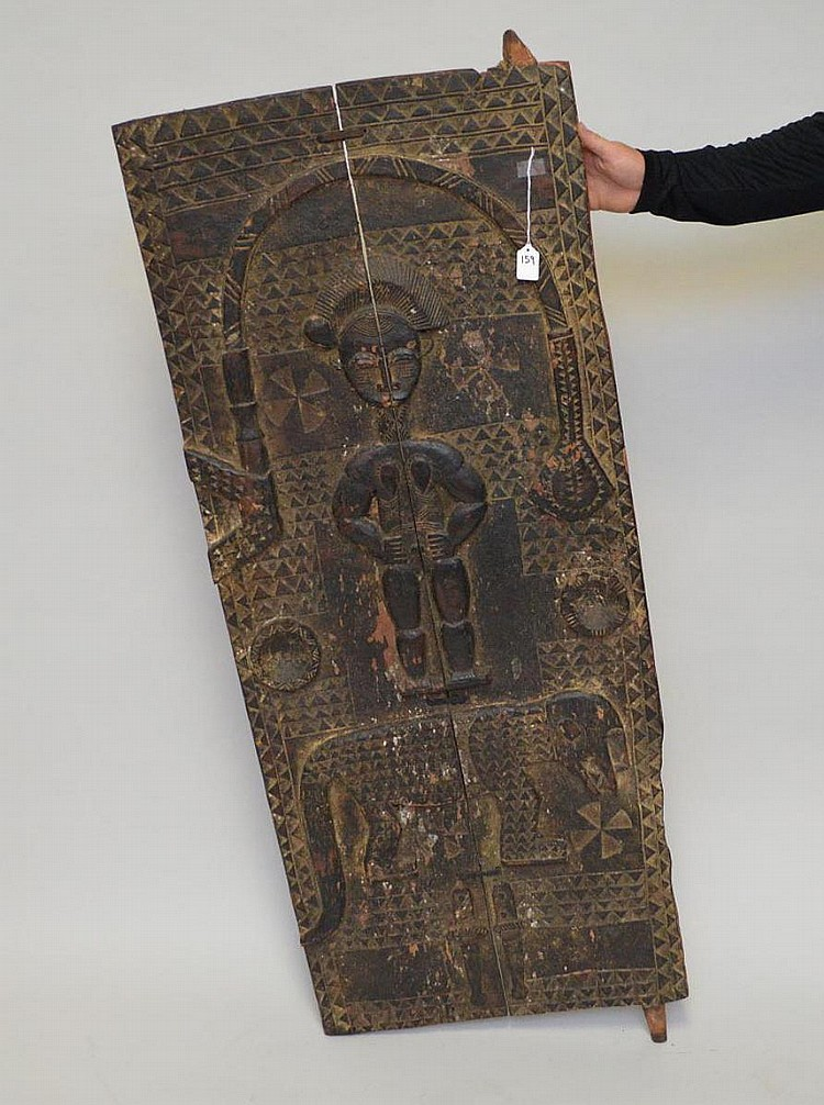 Antique Carved Wood African Door. The carving depicting a woman, cheetah and snake. Condition: good for it's age. The door was made from two boards the middle being held together by three early metal fasteners. 54